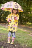 Young girl outdoors in rain with umbrella smiling — Stock Photo