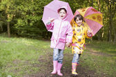 Two sisters outdoors with umbrellas smiling — Stock Photo
