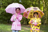 Two sisters outdoors in rain with umbrellas smiling — Stock Photo