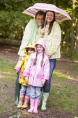 Family outdoors in rain with umbrella smiling — Stock Photo