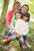 Family outdoors in woods sitting on log smiling — Stock Photo