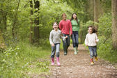 Family walking on path holding hands smiling — Foto Stock