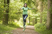 Woman jumping on path smiling — Stock Photo