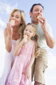 Family standing outdoors with ice cream — Stock Photo