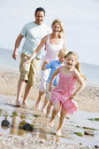 Family running at beach smiling — Stock Photo