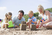 Family on beach making sand castles smiling — Stock Photo