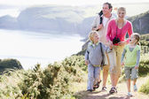 Family walking on cliffside path holding hands and smiling — Stock Photo