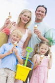 Family at beach with ice cream cones smiling — Stock Photo