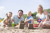 Family on beach making sand castles smiling — Stock fotografie