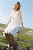 Woman sitting on fence outdoors smiling — Stock Photo