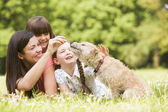 Mother and daughters in park with dog smiling — Stok fotoğraf