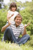 Father and daughter sitting outdoors with flowers smiling — Stock Photo