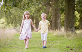 Two young children walking on path holding hands smiling — Stock Photo