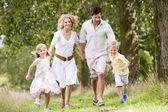 Family running on path holding hands smiling — Stock fotografie