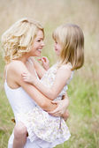 Mother holding daughter outdoors smiling — Stok fotoğraf