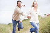 Couple running at beach smiling — Stock Photo