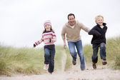 Father and two young children running at beach smiling — Stock Photo