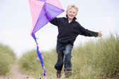 Young boy running on beach with kite smiling — Stock Photo