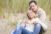 Pareja sentada en la playa sonriendo — Foto de Stock