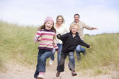 Family running on beach smiling — Stock Photo