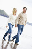 Couple walking on beach holding hands smiling — Stock Photo