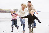 Family running on beach holding hands smiling — Foto Stock