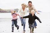 Rodzina działa na plaży gospodarstwa ręce uśmiechając się — Zdjęcie stockowe