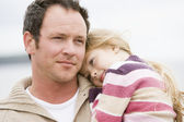 Father holding daughter at beach — Stockfoto