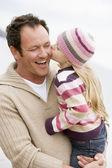 Far anläggning dotter kyssa honom på stranden leende — Stockfoto