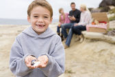 Family at beach with picnic smiling focus on boy with seashells — Stock Photo