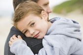 Father holding son at beach — Stock Photo
