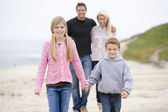 Family walking at beach holding hands smiling — Stock Photo