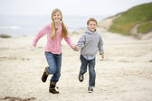 Two young children running on beach holding hands smiling — ストック写真
