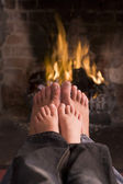 Father and son's feet warming at a fireplace — Stock Photo