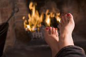 Feet warming at a fireplace — Stok fotoğraf