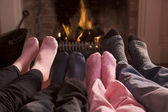 Family of Feet warming at a fireplace — Stockfoto