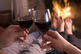 Feet warming at fireplace with hands holding wine — Stockfoto
