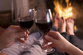 Pés na lareira o aquecimento com as mãos segurando o vinho — Foto Stock