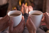 Feet warming at fireplace with hands holding coffee — Stockfoto