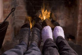 Couple's feet warming at a fireplace — Stock Photo