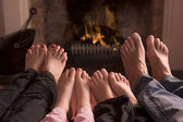 Family of feet warming at a fireplace — Stock Photo