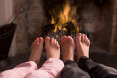 Children's feet warming at a fireplace — Stock Photo