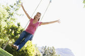 Woman on tree swing smiling — Stock Photo