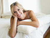 Woman lying in bedroom smiling — Stock Photo