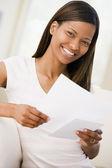 Vrouw in woonkamer lezen kranten glimlachen — Stockfoto