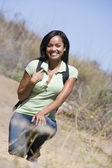 Woman crouching on beach path smiling — Stock Photo