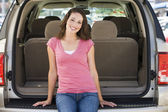 Woman sitting in back of van smiling — Stok fotoğraf
