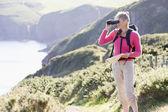 Woman on cliffside path using binoculars — Stock Photo