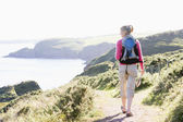 Woman walking on cliffside path — Stock Photo