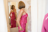 Woman trying on dresses and frowning — Stock Photo
